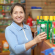 Stock Photo: Womchooses chemicals at shop