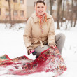 Woman cleans carpet with snow i — Stok fotoğraf