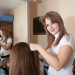 Stylist works on woman hair — Stok fotoğraf