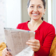 Cheerful mature woman  with newspaper   — Stock Photo