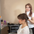 Female hairdresser works on woman hair — Stock Photo