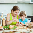 Stock Photo: Womwith child cooking fish pelmeni (pelmeni), always together