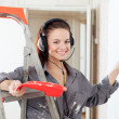 Happy woman in headphones paints wall — Stock Photo
