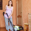 Pregnant woman cleaning her living room — Stock Photo