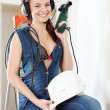 Smiling sexy girl in headphones with drill and hardhat — Stock Photo
