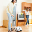 Happy middle-aged couple doing housework — Stock Photo