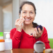 Woman puts facepowder   — Stock Photo