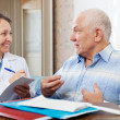Stock Photo: Friendly mature doctor talks with senior man