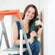Happy girl in dungarees with drill — Stock Photo