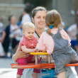 Happy mother with two children on swing — Stock Photo