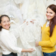 Woman helps the bride in choosing bridal clothes — Stock Photo