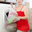 Housewife in red doing laundry — Stock Photo