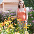 Pregnant woman with lily plant   — Stock Photo