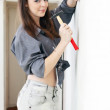 Woman wants to drive screw into wall — Stock Photo
