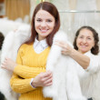 Consultant helps girl chooses fur cape at shop — Zdjęcie stockowe