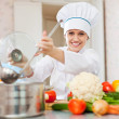 Happy cook in toque works with ladle — Stock Photo