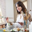 Stock Photo: Smiling female artist paints picture