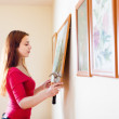 Long-haired girl hanging pictures — Stock Photo #32309621