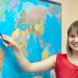 Woman showing something on world map  — Stock Photo