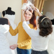 Shop consultant helps girl chooses white bridal outfit — Стоковая фотография