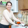 mature woman cleans the gas-stove  — Stock Photo