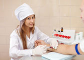 Nurse taking blood sample from patient in clinic — Stock Photo