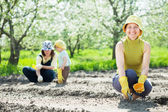 Women and kid sows seeds in soil — Stock Photo