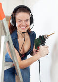 Happy sexual girl in headphones with drill — Stock Photo