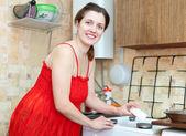 Dona de casa em vermelho limpa o fogão a gás — Foto Stock