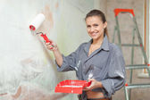 Happy girl paints wall — Stock Photo