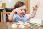 Cute little girl learning to sculpt dough figurines — Stock Photo