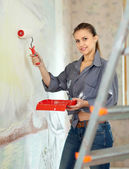 Woman paints wall with roller at home — Stock Photo