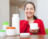 Woman uses cosmetic cream — Stock Photo