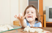 Baby girl sculpting from clay or dough in home — Stock Photo