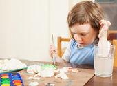 La niña pinta las figurillas de pasta — Foto de Stock