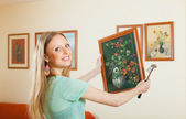 Young woman hanging the art picture — Stock Photo