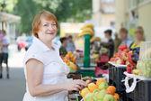 Woman chooses fruits at market — Stock Photo