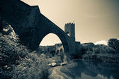 Medieval stone bridge over river. Imitation of old image — Stock Photo