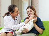 Friendly mature pediatrician doctor examining newborn — Stock Photo