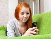 Girl uses mobile in home — Stock Photo