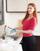 Smiling woman washing dishes — Stock Photo