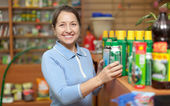 Woman chooses chemicals at shop — Stock Photo