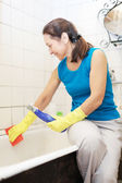 Woman cleans bathtub with rug — Stock Photo