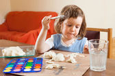 Cute little girl learning to paint dough figurines — Stock Photo