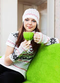 Woman in hat warms with cup of tea — Stock Photo