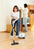 Happy woman and man doing housework — Stock Photo