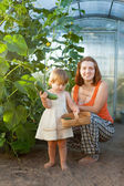 Woman and baby girl with cucumber harvest — Stock Photo