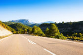 Asphalt road through mountains — Stock Photo