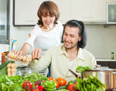 Friendly married couple preparing a meal of vegetables — Stock Photo