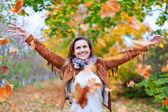 Mutlu kadın sonbahar yaprakları atar — Stok fotoğraf